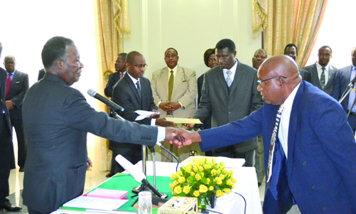 President Sata congratulating Munkombwe after swearing him