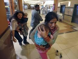 Women carrying children run for safety as armed police hunt gunmen who went on a shooting spree in Westgate shopping centre in Nairobi September 21, 2013. (Photo by Goran Tomasevic/Reuters)