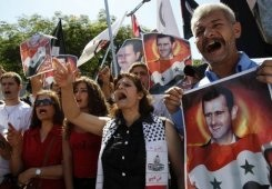 Protesters hold portraits of Syrian President Bashar al-Assad during a demonstration in Beirut, on September 8, 2013