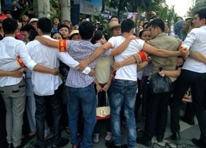 Vietnamese plainclothes police form a human chain to prevent hundreds of protestors from approaching the People's Court where Vietnamese activist lawyer Le Quoc Quan faces charges of tax evasion in Hanoi on October 2, 2013/AFP