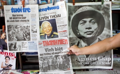 A man picks up a newspaper with pictures of Vietnamese general Vo Nguyen Giap on the front page at a newspaper stall in Hanoi, Vietnam. Photo: EPA
