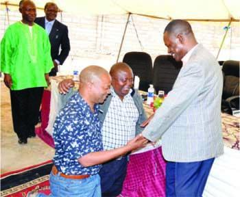 Chikwelete on his knees(l) with former Lusaka District Chairman Goodson Banda before Kabimba