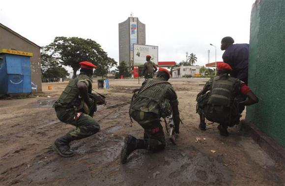 Congolese security officers position themselves as they secure the street near the state television headquarters (C) in the capital Kinshasa, December 30, 2013. Credit: REUTERS/Jean Robert N'Kengo