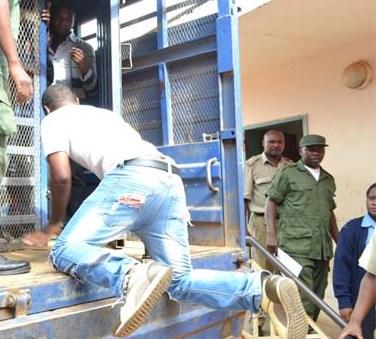 General Kanene boarding into a prison truck
