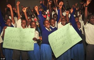 Arms raised: Ugandan pupils from different schools take part in an event organised by Christians to celebrate the signing of a new anti-gay