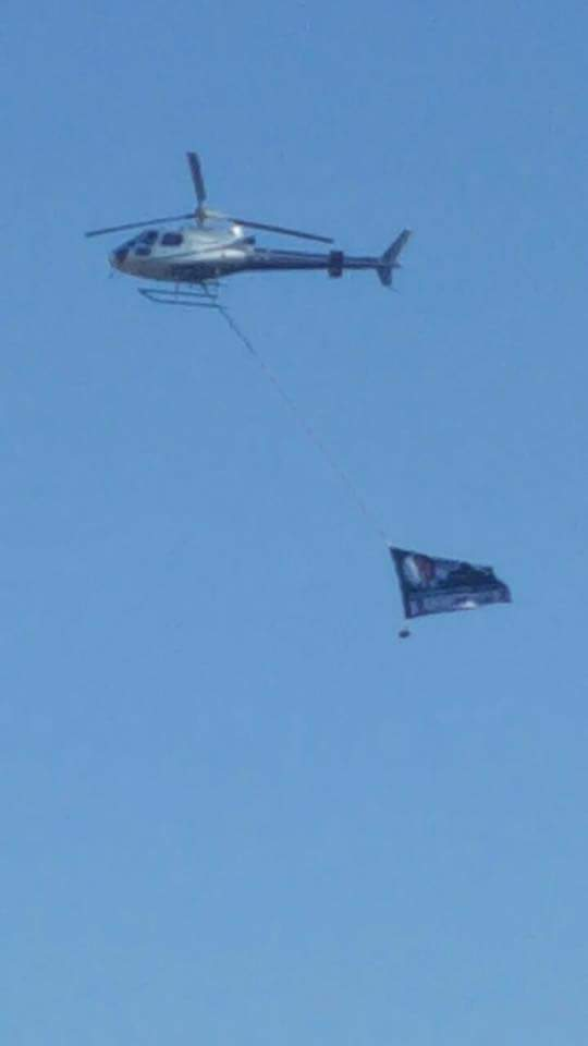 A chopper dragging a PF banner flies over the UPND rally in Chawama