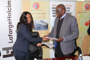 Lafarge Zambia CFO Mrs Chrissie Moloseni and the ZRL CEO Mr Christopher Musonda exchanging the Transport Agreement